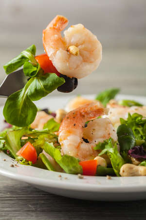Shrimp salad with tomato, olives and cashew nuts. Front view. Close-up.
