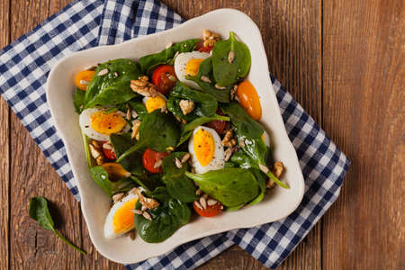 Delicious salad of fresh spinach, boiled egg, tomatoes, nuts and sunflower seeds. Top view.