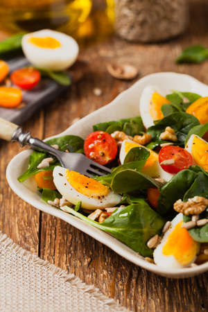 Delicious salad of fresh spinach, boiled egg, tomatoes, nuts and sunflower seeds. Front view.