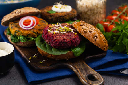 Vege burgers with carrots, beetroots and mushrooms. Front view. Black background. Stock Photo