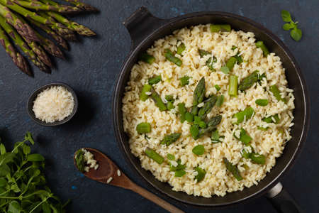 Classic Italian risotto with asparagus. Top view. Dark blue background.
