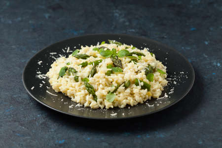 Classic Italian risotto with asparagus. Front view. Dark blue background. 写真素材