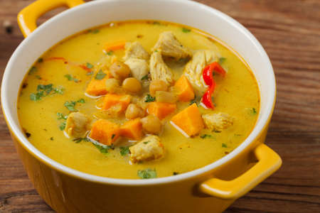Sweet potato soup with chicken and lentils. Front view. Natural wooden background.