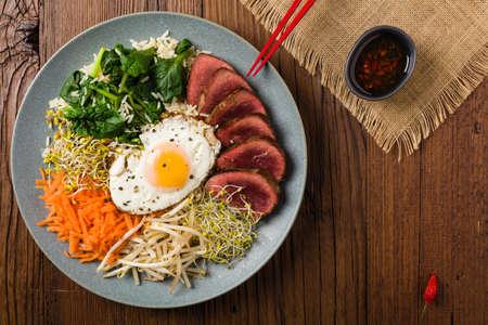 Koreanisches Rindfleisch mit Sprossen, Spinat und Spiegelei. Ansicht von oben.