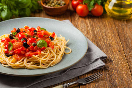 Italian spaghetti alla Pultanesca with tomatoes and olives. Served without meat and cheese. Front view. Natural wooden background.
