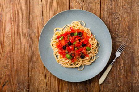 Italian spaghetti alla Pultanesca with tomatoes and olives. Served without meat and cheese. Top view. Natural wooden background. 写真素材