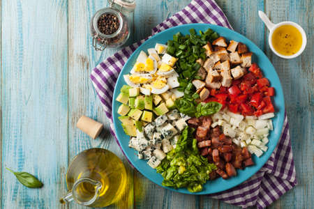 Cobb salad.  Main-dish American garden salad typically made with chopped salad greens , tomato, crisp bacon, boiled, grilled chicken breast, hard-boiled eggs, avocado, chives, Roquefort cheese, and red-wine vinaigrette. Top view.