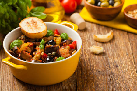 Traditional Italian caponata, served with croutons in a yellow, sunny pot. Decorated with basil and pine nuts. Front view. Stock fotó