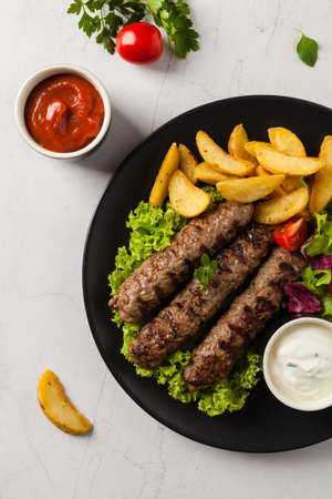 Traditional cevapcici served with baked potatoes. Flat lay. Stone background. Top view. Stock fotó