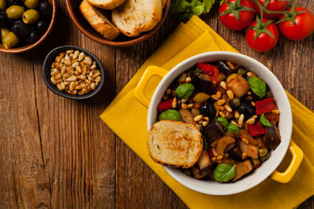 Traditional Italian caponata, served with croutons in a yellow, sunny pot. Decorated with basil and pine nuts. Top view. Stock fotó