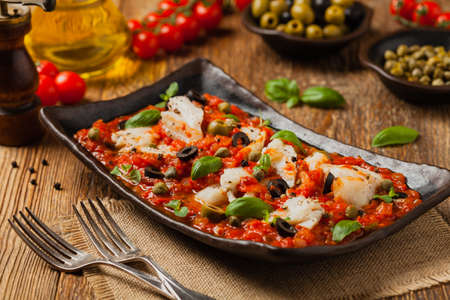 Cod in Italian in tomatoes with olives and capers. Front view.