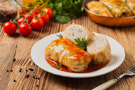 Traditional stuffed cabbage with minced meat and rice, served in a tomato sauce. Front view.