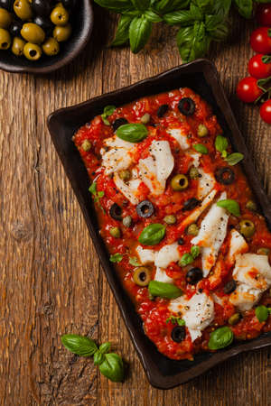Cod in Italian in tomatoes with olives and capers. Top view.