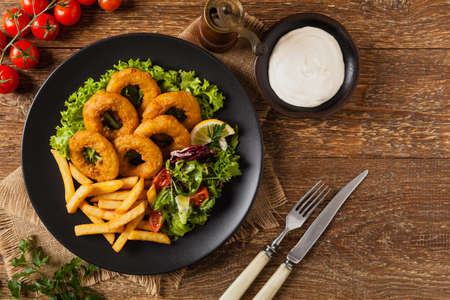 Roasted squid rings with fries. Top view