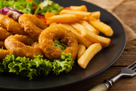 Roasted squid rings with fries. Front view