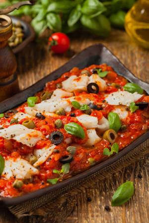 Cod  in tomatoes with olives and capers. Front view.