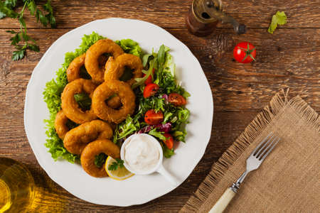 Roasted squid rings with salad. Top view.