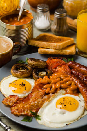 Full English breakfast, with sausage, mushrooms, beans and a fried egg. Front view.