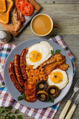 Full English breakfast, with sausage, mushrooms, beans and a fried egg. Top view.