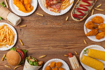 Mix of fast food, street dishes. Background with copy space. Top view. Natural wooden background.