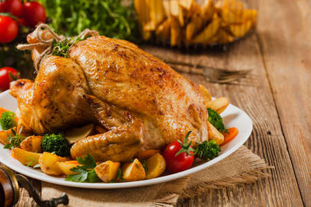Roasted chicken. Served on a plate with vegetables and baked potatoes.