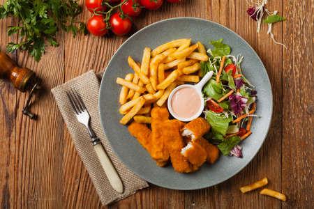 Bastoncini di pesce con patatine fritte e insalata su lastra grigia. Vista dall'alto.