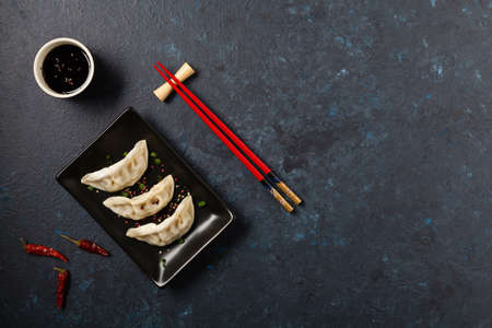 Original Japanese dumplings Gyoza with chicken and vegetables. Top view. Flat lay. Dark blue backgrund. Stockfoto