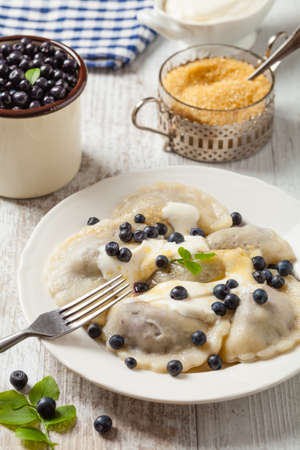 Delicious dumplings with fresh blueberries served with whipped cream and sugar or sauce. Bright, wooden background. Front view.