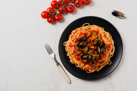 Spaghetti with mussels. Top view. Stone background.