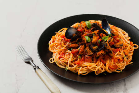 Spaghetti with mussels. Front view. Stone background.