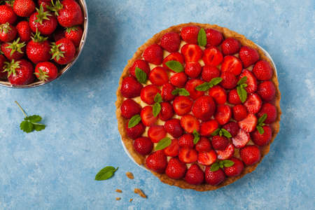 Delicious tart with strawberries on a blue painted background. Top view.