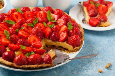Délicieuse tarte aux fraises sur fond bleu peint. Vue de face.