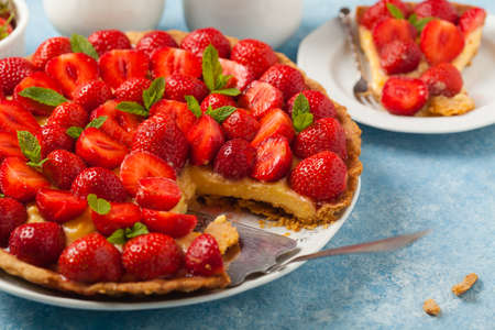 Delicious tart with strawberries on a blue painted background. Front view.