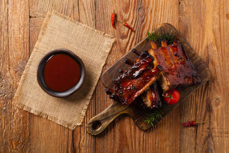 Roasted pork ribs in a bbq sauce. Served on a wooden board. Top view.