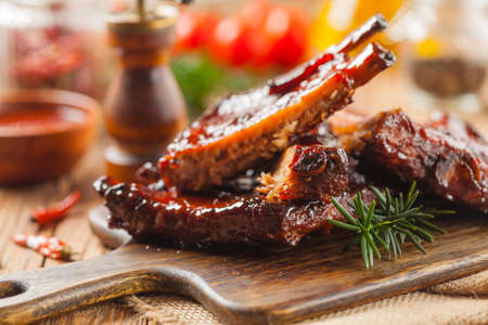Roasted pork ribs in a bbq sauce. Served on a wooden board. Front view. Imagens