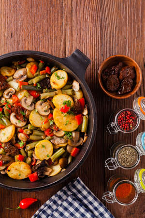 Fried pan vegetables, with mushrooms and dried tomatoes. Seasoned with a mix of herbs. Top view.