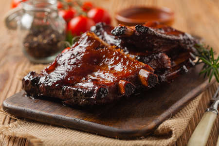 Roasted pork ribs in a bbq sauce. Served on a wooden board. Front view. Stok Fotoğraf - 130073734