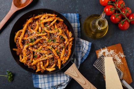 Maccheroni al ferretto with beef in ragu bolognese. Top view.