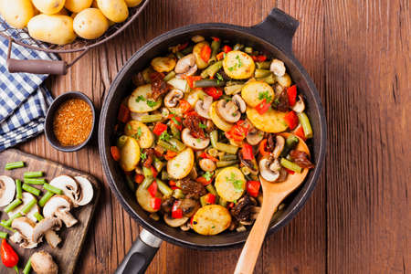 Fried pan vegetables, with mushrooms and dried tomatoes. Seasoned with a mix of herbs.Top view. Stok Fotoğraf - 130134702