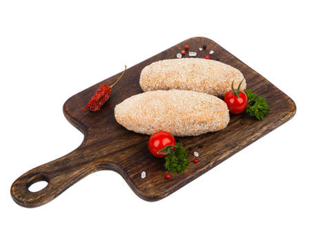 Raw poultry chop devolay with butter. Shown on a brown chopping board. Breaded in a bun. Pack shot. White background.