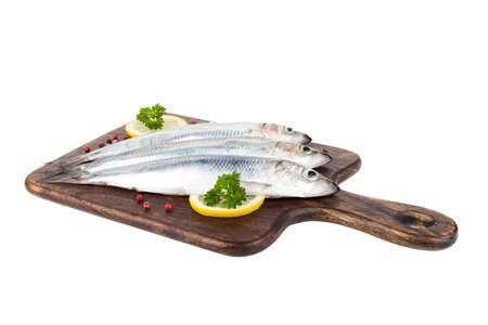 Raw herrings on a wooden board. White background. Isolated. Stockfoto