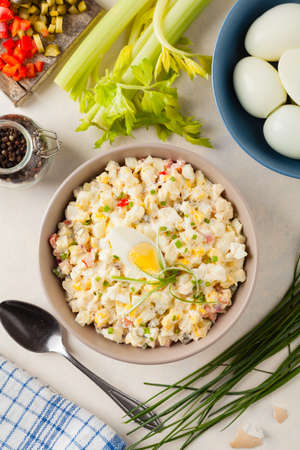 A light egg salad with celery, gherkin, pepper and mayonnaise. Served in a bowl on a light background. Top view. Foto de archivo