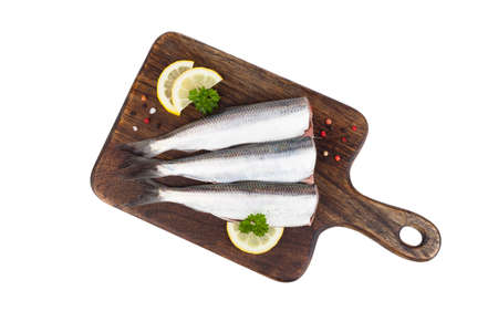 Herring fillet on a wooden board, decorated with lemon, parsley and spices.