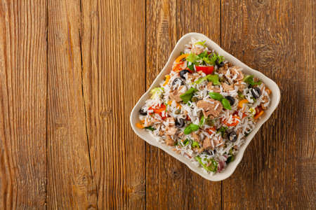 Italian tuna salad with rice, olives and capers. Top view. Natural wooden background.