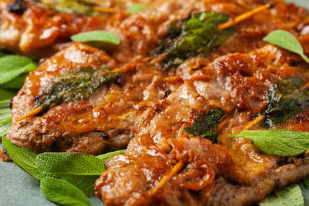 Saltimbocca. Veal schnitzel with sage and Parma ham. Italian specialty. Front view. Close up.