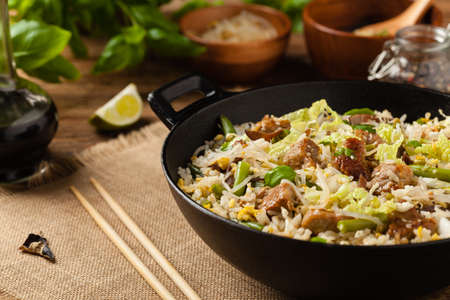 Fried veal, with rice, Chinese cabbage and mushrooms. Sprinkled with sesame and soy sauce. Front view.