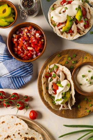 Mini tortillas with tomato salsa, avocado and boiled chicken. Top view.  Stock Photo