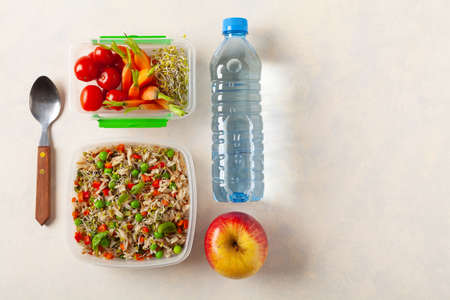 Trendy lunch with rice and vegetables. Served in a portable box on a bright painted background. Perfect for work or school. Top view.