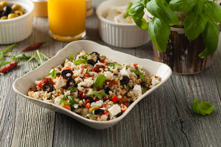 Trendy lunch with red rice, a mix of groats and vegetables. Front view. Served in white bowl on grey wooden background.