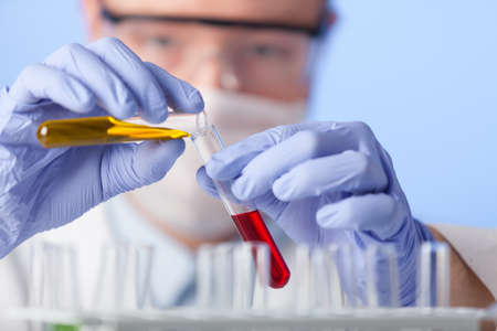 A lab technician in a white coat and rubber gloves and protective glasses is investigating the effect of the substance on the reagent.